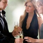 Young man with two glasses with champagne and two women standing